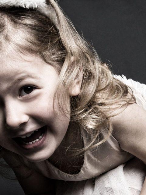 kleines Mädchen lacht in Kamera, fotografiert von Doreen Schmitt